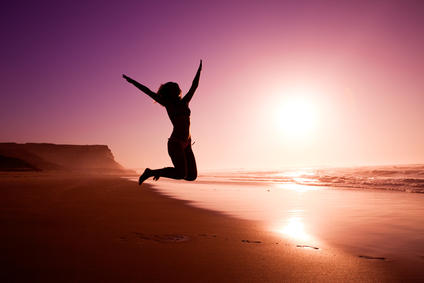 Woman in silouette jumping on beach
