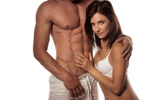 Woman in white bra with hand on man's abs
