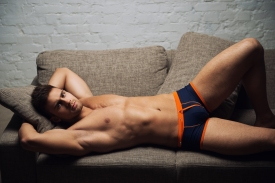 Shirtless guy on couch with orange black undies