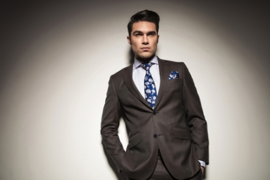 Young elegant business man leaning on a grey wall with his hands in pockets, looking away from the camera.