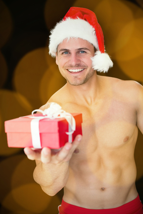 Smiling muscular man posing in sexy santa outfit offering gift against blurry yellow christmas light circles
